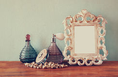 Vintage antigue perfume bottles with old picture frame, on wooden table. retro filtered image.  Royalty Free Stock Images