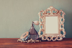 Vintage antigue perfume bottles with old picture frame, on wooden table. retro filtered image. Vintage antigue perfume bottles with old picture frame, on wooden Stock Photography