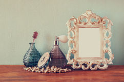 Vintage antigue perfume bottles with old picture frame, on wooden table. retro filtered image.  Stock Photo