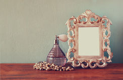 Vintage antigue perfume bottles with old picture frame, on wooden table. retro filtered image.  Stock Images