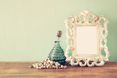Vintage antigue perfume bottles with old picture frame, on wooden table. retro filtered image. Vintage antigue perfume bottles with old picture frame, on wooden Stock Photos