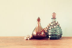 Vintage antigue perfume bottles, on wooden table. retro filtered image Stock Photography