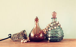Vintage antigue perfume bottles, on wooden table. retro filtered image. Vintage antigue perfume bottles, on wooden table. retro filtered image Royalty Free Stock Images