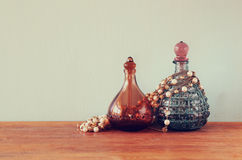 Vintage antigue perfume bottles, on wooden table. retro filtered image.  Royalty Free Stock Photo