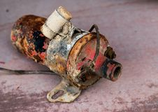 Vintage antique automotive ignition coil with bracket and suppression condenser with rust and peeling paint. Vintage antique automotive ignition coil with Stock Image