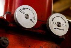 Vintage antique automotive machine shop hydraulic press pressure valve dials. On a red press Stock Photos