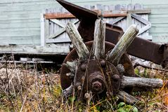 Vintage antique automotive tractor broken wood wheel spokes and hub covered in rust. And oxidation from age Stock Image