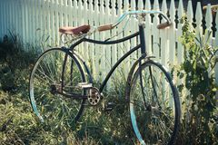 Antique bicycle leaning on a fence. Vintage or antique bicycle with a red seat leaning on a white picket fence Stock Photos
