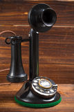 Vintage, antique candlestick telephone with dial on wood background Royalty Free Stock Photography