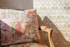 Vintage antique chair with colorful print wallpaper Royalty Free Stock Image