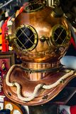 Vintage antique copper diving helmet displayed in store glass window. Historic nautical accessories traveling concept stock images
