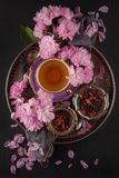 Vintage, antique cup of fruit tea decorated with cherry flowers on black background with antique plates