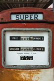 A vintage antique Gasoline fuel pump on red Royalty Free Stock Photo