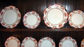 Vintage antique plates in a kitchen cupboard Royalty Free Stock Image