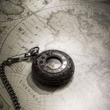 Vintage antique pocket watch on old map background. Close up Royalty Free Stock Photography