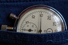Vintage antiques Stopwatch, in dark old blue denim pocket, value measure time, old clock arrow minute, second accuracy timer recor Stock Images