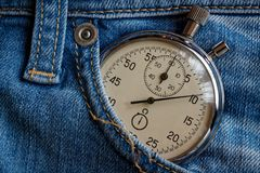 Vintage antiques Stopwatch, in old worn dark blue denim pocket, value measure time, old clock arrow minute, second accuracy timer Stock Images