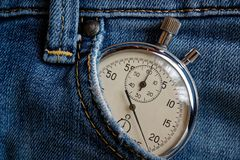 Vintage antiques Stopwatch, in old worn dark blue jeans pocket, value measure time, old clock arrow minute, second accuracy timer Stock Photo