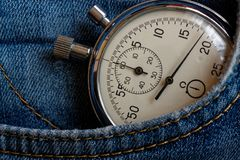 Vintage antiques Stopwatch, in old worn dark blue denim pocket, value measure time, old clock arrow minute, second accuracy timer Stock Image