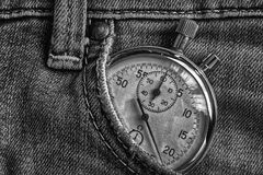 Vintage antiques Stopwatch, in old worn denim pocket, value measure time, old clock arrow minute, second accuracy timer record. Vintage antiques Stopwatch, in Stock Image