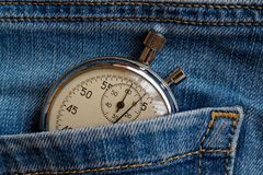 Vintage antiques Stopwatch, in worn dark blue denim pocket, value measure time, old clock arrow minute, second accuracy timer reco Stock Image