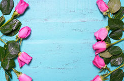 Vintage aqua blue wood background with pink rose buds.