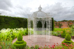 Vintage arbour in a garden. White wrought iron arbour in an English garden with flowers and topiary shrubs Stock Image
