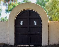 Arched adobe gate with wooden door in California. Vintage arched adobe gate with brown wooden doors outside a mission in California Royalty Free Stock Photos