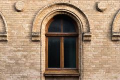 Vintage arched window in the wall of yellow brick. Black glass in a maroon dark red wooden frame. The concept of antique. Vintage architecture in building Stock Photography