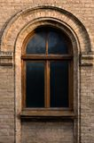 Vintage arched window in the wall of yellow brick. Black glass in a maroon dark red wooden frame. The concept of antique. Vintage architecture in building Stock Photo