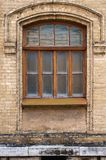 Vintage arched window in the wall of yellow brick. Black glass in a maroon dark red wooden frame. The concept of antique. Vintage architecture in building Stock Image