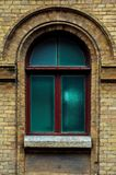 Vintage arched window in the wall of yellow brick. Green - the colors of sea wave glass in a maroon dark red wooden. Frame. The concept of antique vintage Royalty Free Stock Image