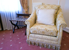 Vintage armchair. A vintage armchair on red carpet, hotel room interior Royalty Free Stock Image