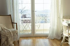 Vintage armchair against white wall and big window with curtain. stock photography