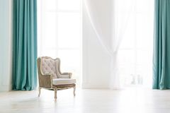 Vintage armchair against white wall and big window with curtain. Space for your copy royalty free stock photo