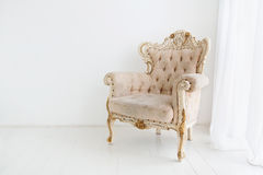 Vintage armchair against white wall in white room Stock Images
