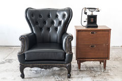 Vintage armchair and telephone on white wall. Black vintage armchair and telephone on white wall Stock Photography