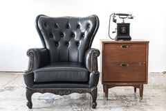 Vintage armchair and telephone on white wall. Black vintage armchair and telephone on white wall Stock Photos