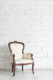 Vintage armchair on white wall. Royalty Free Stock Image