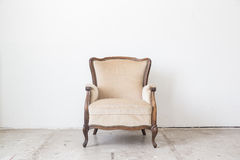 Vintage armchair on white wall. Royalty Free Stock Images