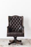 Vintage armchair on white wall. Royalty Free Stock Photos