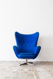 Vintage armchair on white wall. Royalty Free Stock Photo