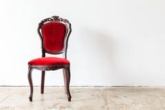 Vintage armchair on white wall. Stock Photo
