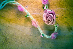 Vintage of artificial flowers rose on the old paper stripes. Stock Photography