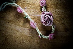 Vintage of artificial flowers rose on the old paper stripes. Vintage of artificial flowers rose on the old paper stripes stock photo