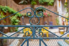 Vintage artistic green wrought iron gate with peeling paint and rust revealing blurred garden. In the background Stock Photos