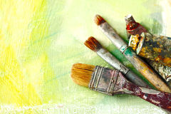 Vintage artists brushes and paint tubes on an abstract artistic background Royalty Free Stock Photos
