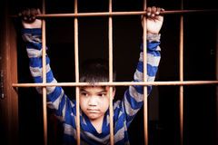 Vintage of asian boy Hand in jail. Looking out the window Stock Photo