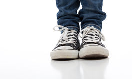 Vintage athletic shoes on white with jeans Royalty Free Stock Image