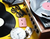 Vintage attributes, 80s media. Vinyl player, video cassettes, audio cassettes, records, radio, vintage alarm clock on a yellow background stock photography